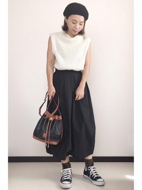 黒ベレー帽とニットベストに黒バルーンスカートを履いた女性
