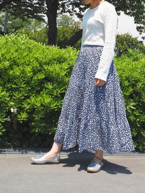 シルバードライビングシューズと白カットソーに小花柄スカートを履いた女性