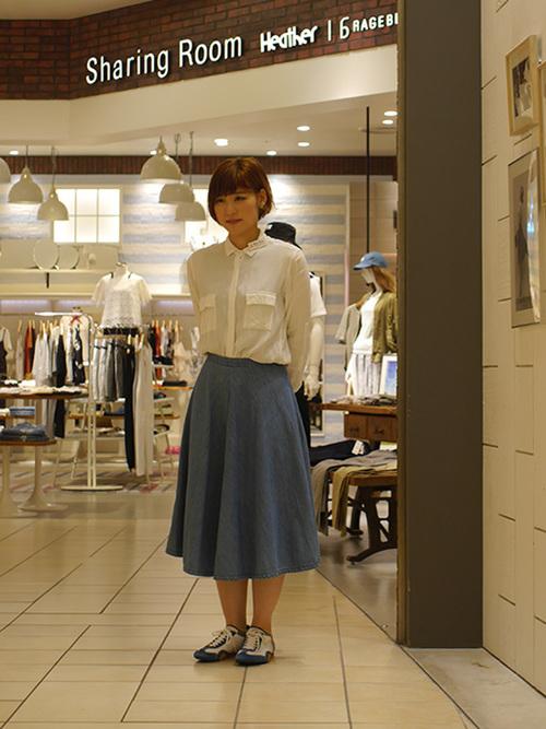 ブルードライビングシューズと白ワークシャツにブルーフレアスカートを履いた女性