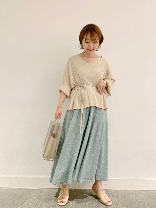 水色ドット柄スカートとベージュツインニットカーディガンにベージュシースルーサンダルを履いた女性