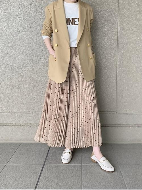 ピンクドット柄プリーツスカートとロゴTシャツにベージュジャケットを着た女性
