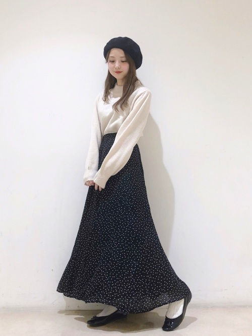 黒ドット柄フレアスカートと白ハイネックニットに黒エナメルバレエシューズを履いた女性