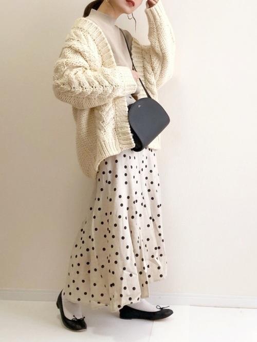 白ドット柄リネン混フレアスカートと白ケーブルニットカーディガンに黒バレエシューズを履いた女性