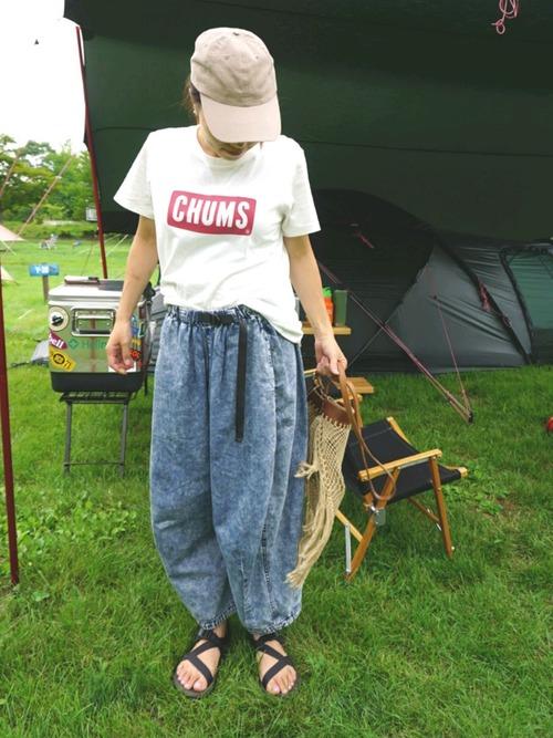 チャムスの赤ロゴTシャツとケミカルパンツに黒クロスサンダルを履いた女性