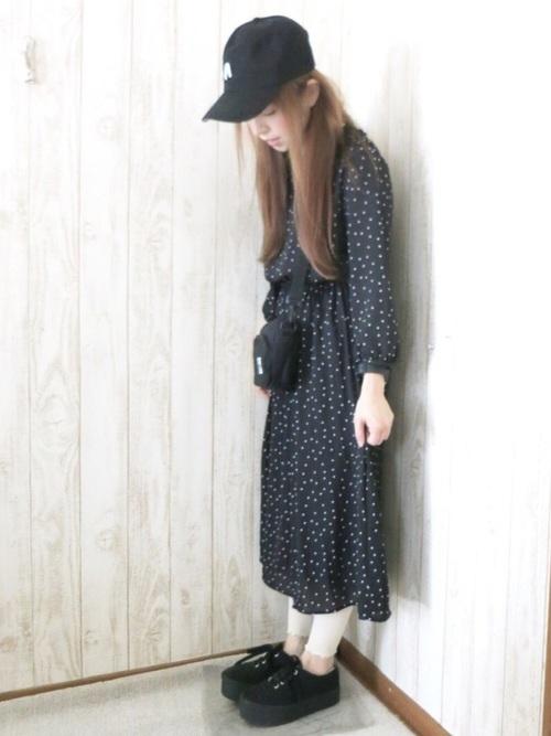チャムスの黒ショルダーバッグと黒ドット柄シフォンワンピースに白リブレギンスを履いた女性