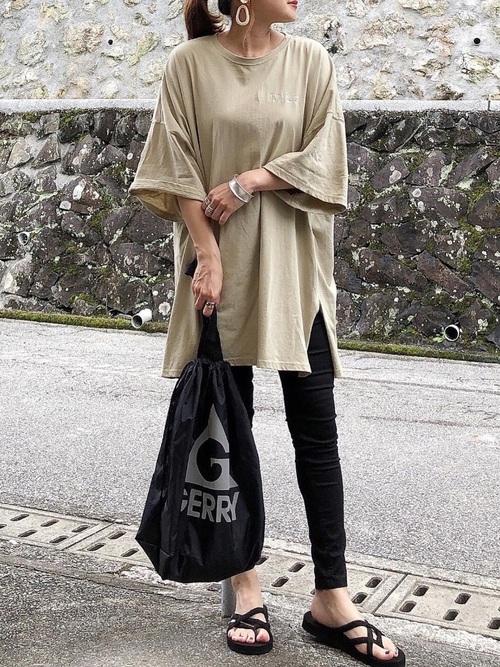 ベージュスリットTシャツと黒スキニーパンツを着た女性