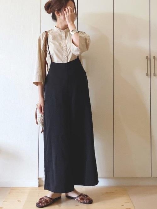 黒サロペットワイドパンツとバンドカラーシャツにベトナムサンダルを履いた女性
