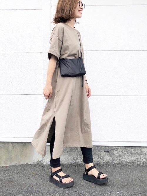 黒サコッシュにベージュTシャツワンピースと黒スキニーパンツを履いた女性
