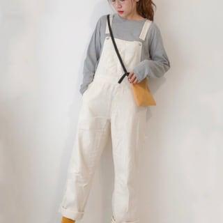 マスタードサコッシュとグレーロングTシャツに白デニムサロペットを履いた女性