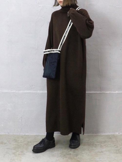 黒キルティングサコッシュとブラウンニットワンピースに黒ドレスシューズを履いた女性