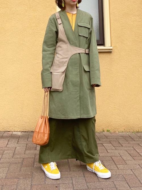 黄色コンバースワンスターとノーカラーコートにカーキロングスカートを履いた女性