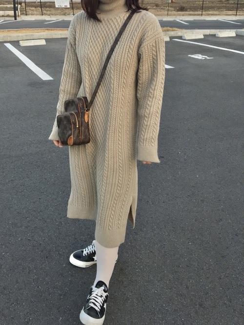 黒コンバースワンスターとケーブルニットワンピースに白タイツを履いた女性