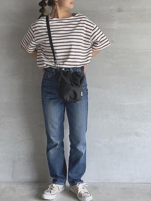 ベージュコンバーススニーカーとデニムパンツにボーダーTシャツを着た女性