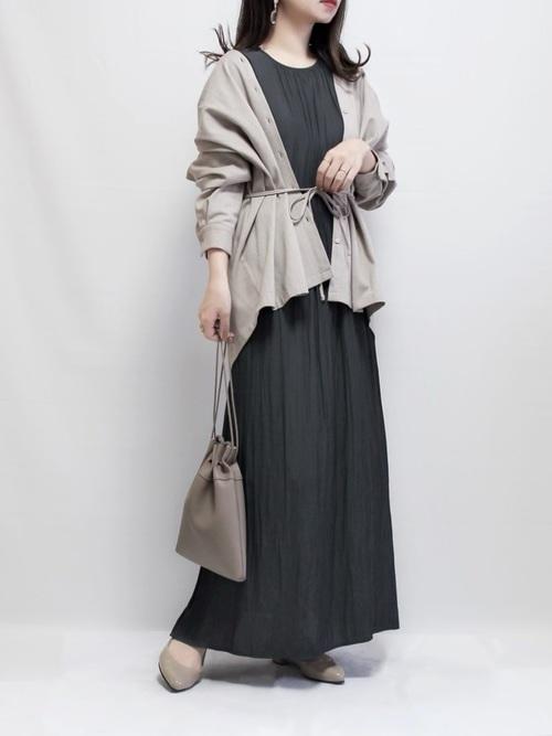 グレーノースリーブワンピースとベージュノーカラーシャツにグレー巾着バッグを合わせた女性
