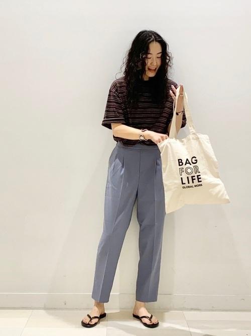 ボーダーTシャツとパンツとエコバッグを着用した女性