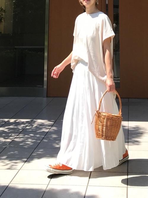 白バッグスリット入りグランTシャツと白ギャザースカートとオレンジローカットスニーカーのトップスコーデの女性