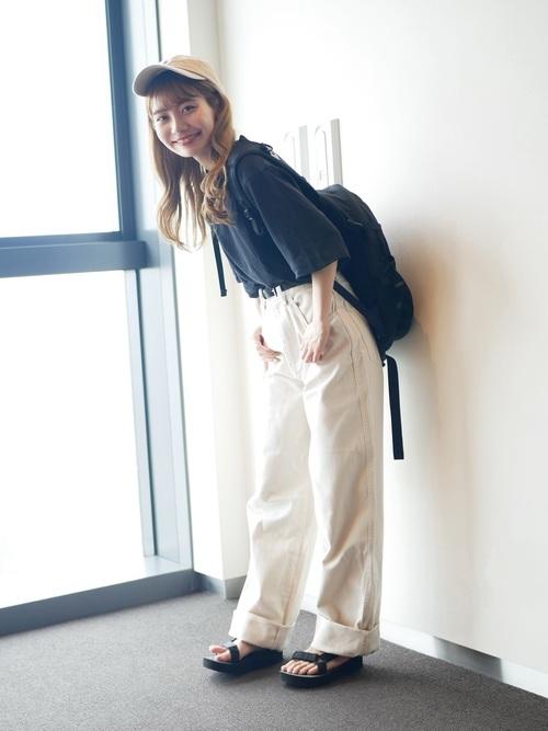 黒コットンリラックスボクシーTシャツと白ワイドフィットカーブパンツと黒リュックのパンツコーデの女性