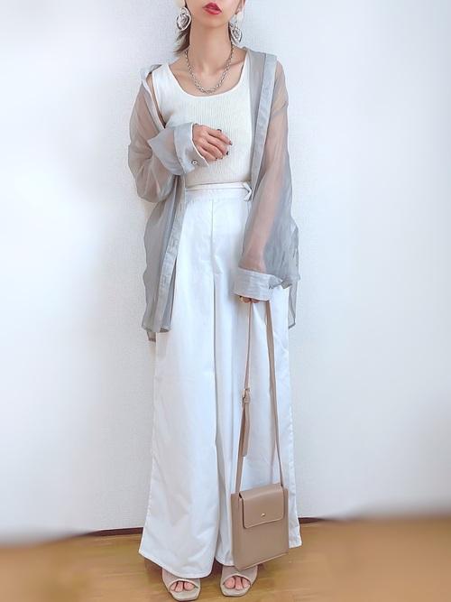 シルバーバンドカラービッグシアーシャツと白ワイドパンツとベージュスクエアミニショルダーバッグのパンツコーデの女性