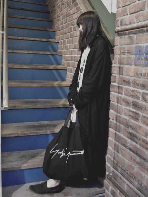 黒ロングガウンと黒ロングスカートとヨウジヤマモトの黒トートバッグコーデの女性