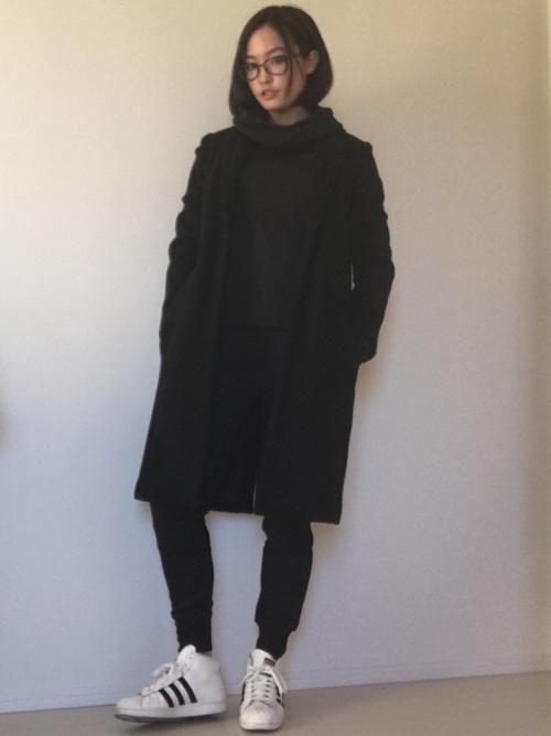 黒チェスターコートと黒NIKEテックフリースパーカーと黒NIKEテックフリースパンツの冬コーデの女性