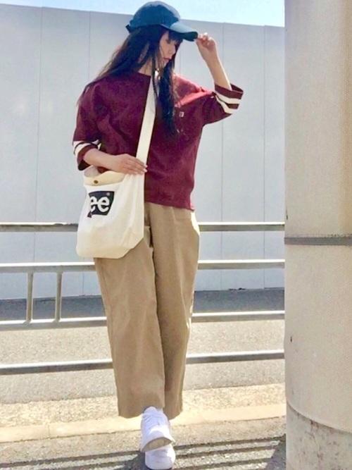 ワインレッド袖ラインカットソーとベージュチノワイドパンツに白スニーカーを履いた女性
