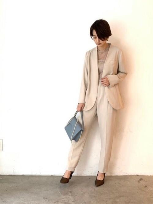 エクリュカラーサイドストラップジャケットとベージュテーパードパンツにブラウンパンプスを履いた女性