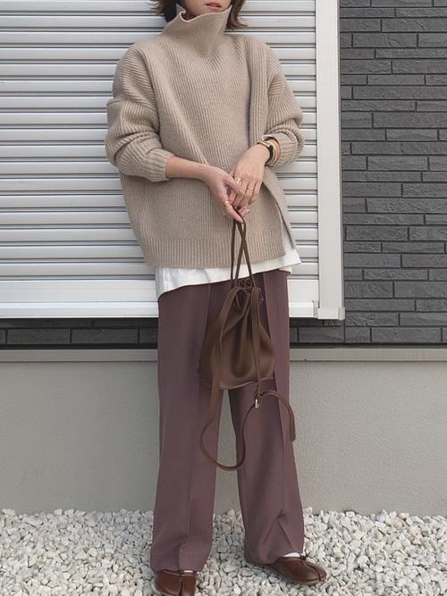 ベージュタートルネックスリットニットとブラウンストレートパンツにブラウン足袋フラットシューズを履いた女性