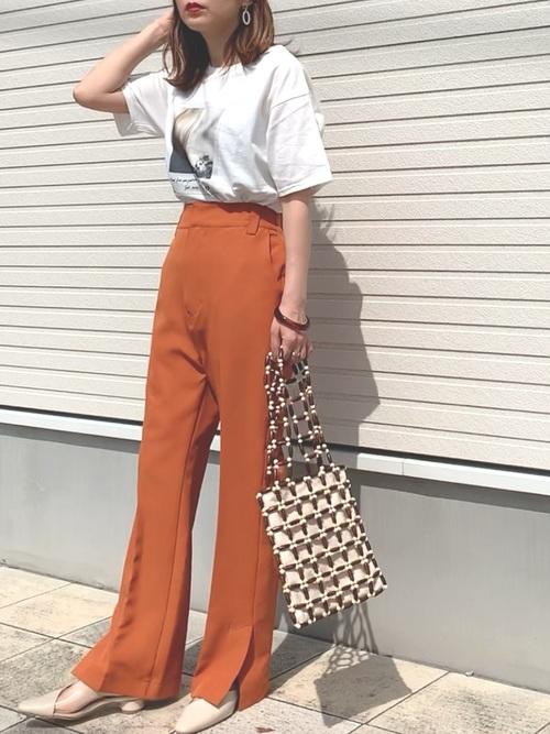 白プリントTシャツとオレンジセンタープレスサイドスリットパンツにウッドビーズトートバッグを合わせた女性