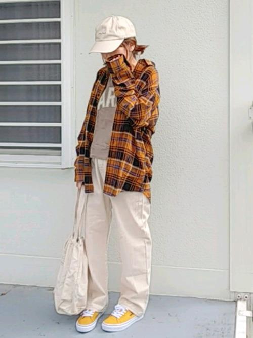 UNIQLOオレンジフランネルチェックシャツとエクリュカラーデニムパンツにイエロースニーカーを履いた女性