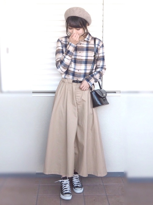 UNIQLOベージュチェックシャツとベージュチノロングスカートに黒ハイカットスニーカーを履いた女性