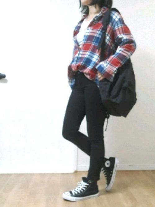 UNIQLO赤フランネルチェックシャツと黒スキニーパンツに黒ハイカットスニーカーを履いた女性