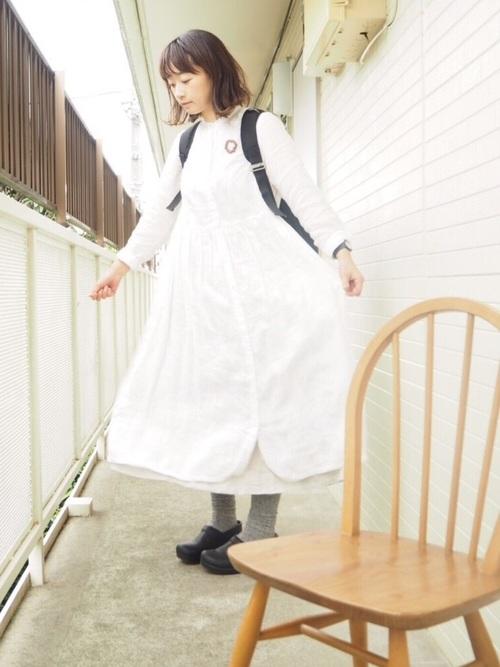 白シャツワンピースと黒マリメッコのリュックBuddyに黒レザーシューズを履いた女性