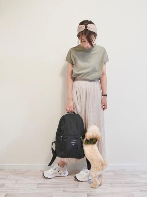カーキUSAコットンTとベージュワッシャープリーツスカートに黒マリメッコのリュックMetroを合わせた女性