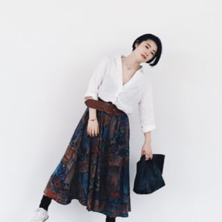 Vネックホワイトシャツとブラウン型押し太ベルトにアートプリントフレアスカートを履いた女性