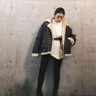 黒ボンバージャケットと白ケーブルニットに黒スキニーパンツを履いた女性