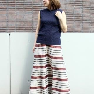 ボーダーロングスカートとケーブルニットノースリーブに黒サンダルを履いた女性