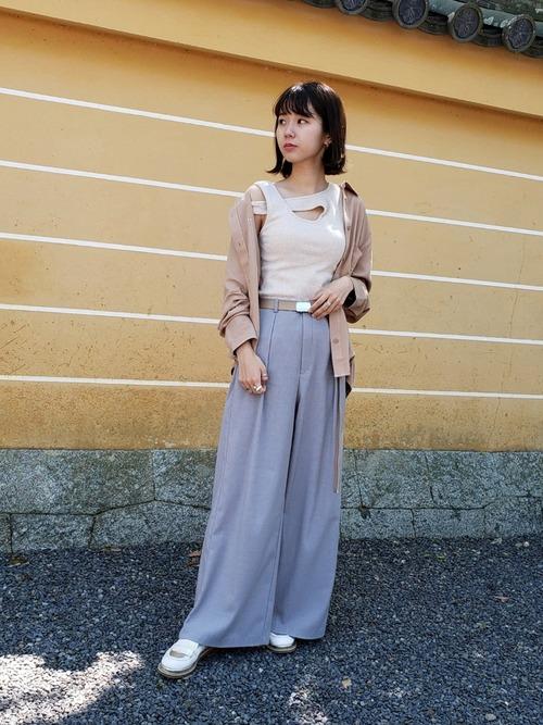 ベルシュカのベージュシャツとアシンメトリータンクトップにグレーワイドパンツを履いた女性