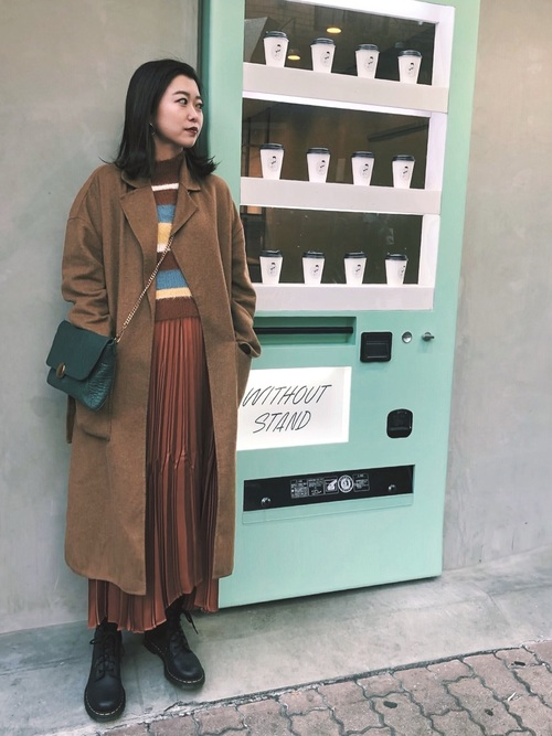 ベルシュカのマルチボーダーニットと茶色チェスターコートに茶色プリーツスカートを履いた女性