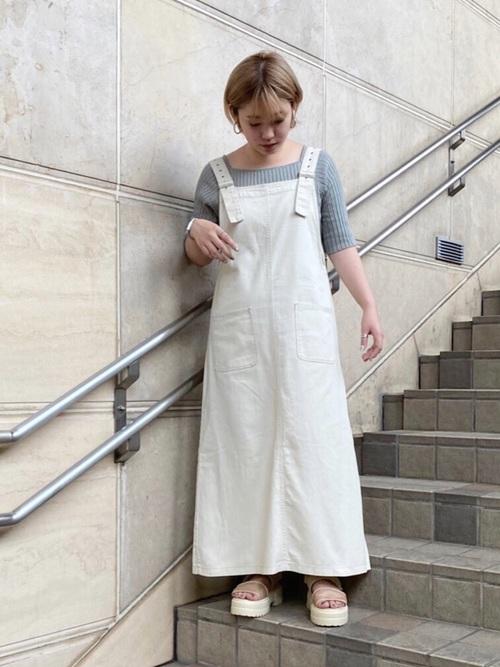 白デニムジャンパースカートとリブサマーニットにベージュサンダルを履いた女性