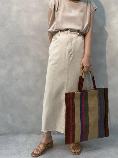 白デニムタイトスカートとベージュノースリーブトップスにベージュサンダルを履いた女性