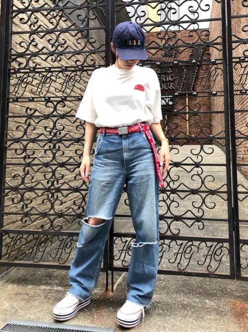 白オーバーサイズプリントTシャツとダメージストレートジーンズに赤ロゴテープベルトを履いた女性