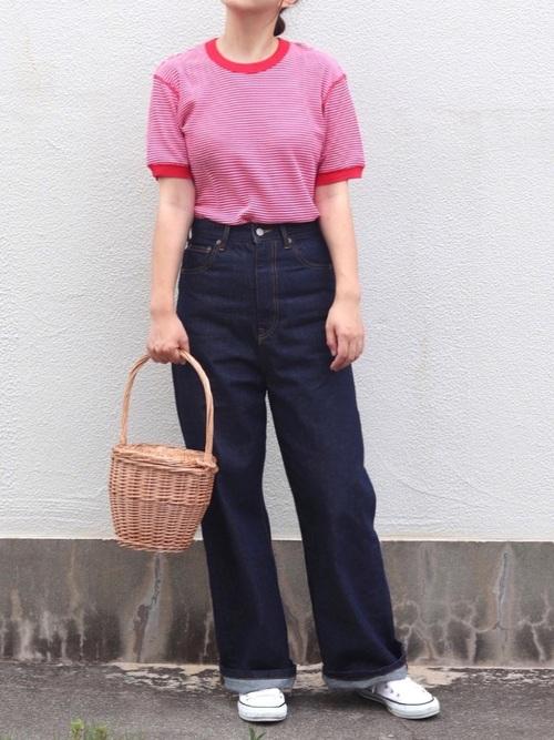 赤ボーダー柄ワッフルTシャツとネイビーストレートルーズジーンズに白スニーカーを履いた女性