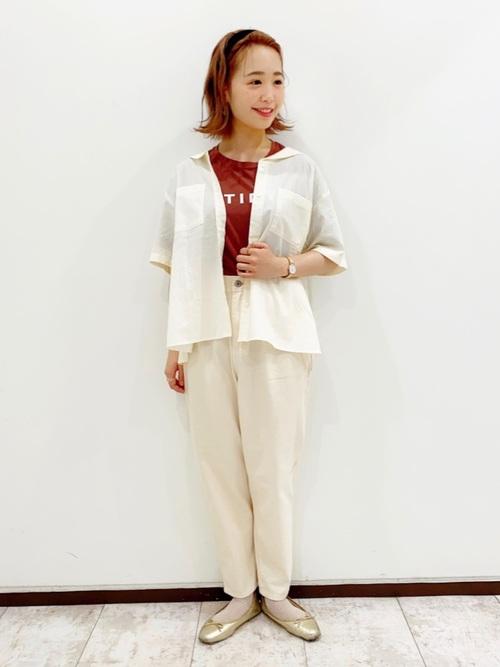 白半袖ワイシャツとロゴ赤Tシャツに白デニムテーパードパンツを履いた女性