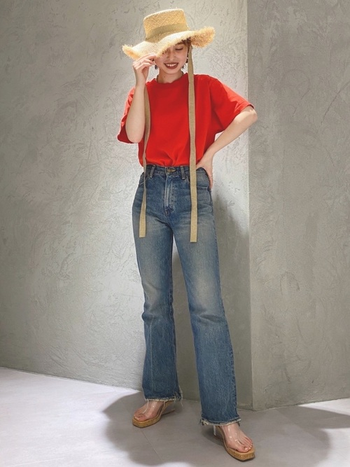 赤ダメージショートTシャツとスリットフレアデニムパンツにリボン付きカンカンハットを履いた女性