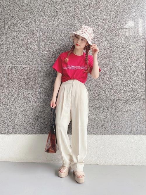 赤半袖ロゴTシャツと白タックワイドパンツに白チェック柄バケットハットを履いた女性