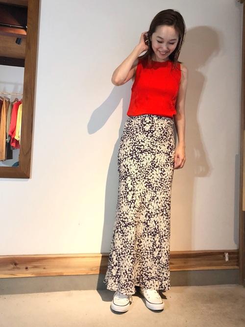 赤ノースリーブカットソーと黒花柄マキシスカートに黒キャンバスハイカットスニーカーを履いた女性