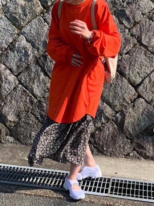 赤ロング丈Tシャツと黒花柄ティアードスカートに白スニーカーを履いた女性
