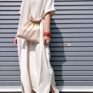 ベージュ裾スリットロングリネンワンピースとベージュドロストバッグにゴールドフラットパンプスを履いた女性