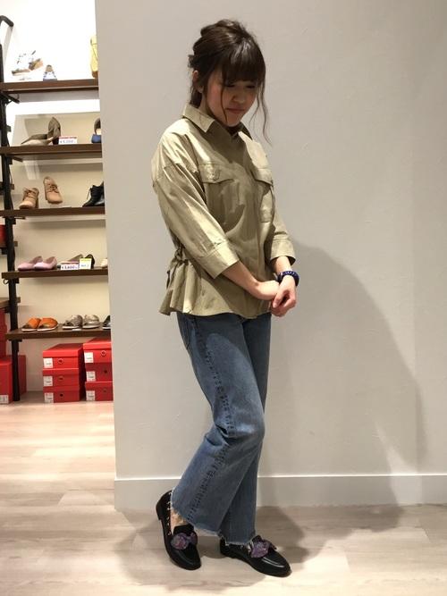 ワークシャツとデニムパンツに黒リボンローファーを履いた女性