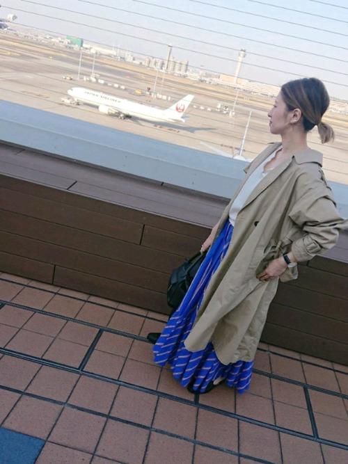 トレンチコートとブルーストライプロングスカートに黒レザー風ハンドバッグを合わせ女性